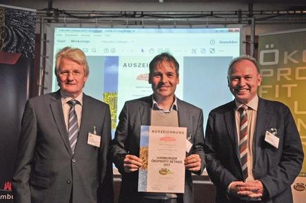 Freut sich über das Zertifikat:: Markhtallen-Geschäftsführer Mike Keller bei der Verleihung mit den Überbringern Uwe Harden (links) und Michael Pollmann (Bild: Markthalle Hamburg)
