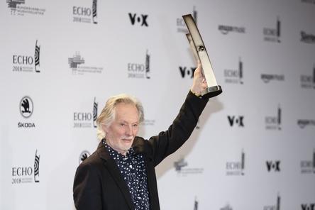 Hier noch mit der Trophäe vor der Siegerwand: Klaus Voormann mit dem Echo für sein Lebenswerk, den der Bassist, Grafiker und Produzent nun zurückgeben will (Bild: Markus Nass/BVMI)