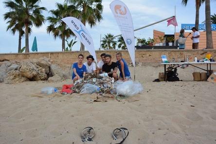 Mit Plastik unter Palmen am Strand von Mallorca: die drei Itchy-Musiker mit zwei OceanCare-Repräsentanten (Bild: OceanCare und Asociación Ondine)