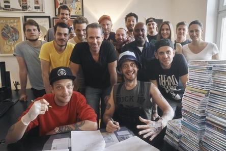 """Trafen sich zur Vertragsunterzeichnung im Kölner WePlay-Office (vorn, von links): Hayo Schauder (Die Boys), Elmar Braun (WePlay), Enno Schauder (Die Boys) und Patrick Kroepels (RNFR/Swutch music) sowie (hinten, von links) Johannes Schlump (Donkong), Tobias Hahn (RNFR/Swutch music), Bastian Meyer (WePlay), Michael Moor (WePlay), Oliver West (RNFR/Swutch music), Skinny (Die Boys), Mikio Gruschinske (WePlay), Benjamin """"Benji"""" Dibaba (Management Die Boys), Thomas Küchler (Donkong), Romina Deeken (WePlay), Josh Silwinski (Management Die Boys) und Nicole Honz (WePlay) (Bild: WePlay)"""