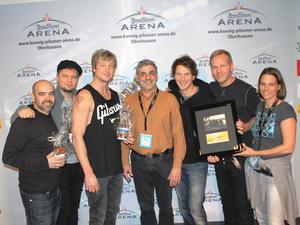 Und auch in Oberhausen gab es einen Preis: Arena-Geschäftsleiter Johannes Partow (Mitte) und Event Direktorin Daniela Stork mit Sunrise Avenue (Bild: König Pilsener Arena)